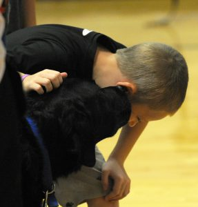 A Fort Plain student talks to Amos the dog during the presentation on Friday.