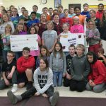 Sixth graders pack and show the money they raised for hurricane relief.