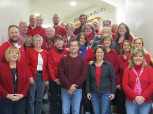 22 smiling adults wearing articles of red clothing standing on the stairs inside the school