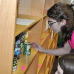 girl removes can of food from shelf