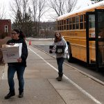 two girls carrying boxes, walking down sidewalk, school bus in background