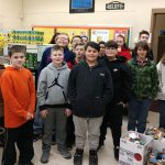 group of students standing in a classroom surrounded by boxes of food