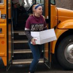 Girl steps off school bus carrying a carton of food