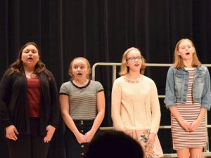 Four high school girls on risers singing