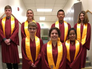 seven high school students dressed in maroon robes with gold
