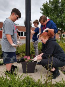 girl and two boys plant flowers in pot outdoors