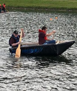 boy and girl paddling a homemade boat