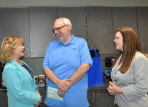 Three colleagues laughing at a retirement party