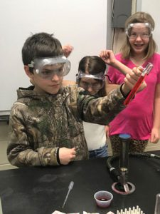 Boy wearing goggles hold a test tube of red liquid over an open flame, two other students look on