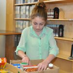 girl arranges canned and boxed foods in a carton