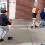 Three boys walk down sidewalk, carrying boxes outside brick school