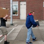 Two boys carrying boxes of food walk down sidewalk outside brick school