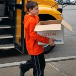 boy steps of school bus carrying box