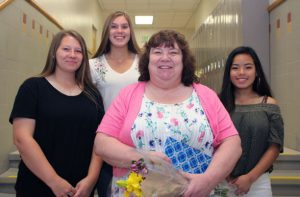 Three high school girls flank woman in school hallway.