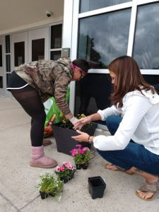 Woman helps boys plant flowers in plastic planter