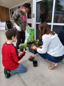 Woman helps two boys plant flowers in plastic planter