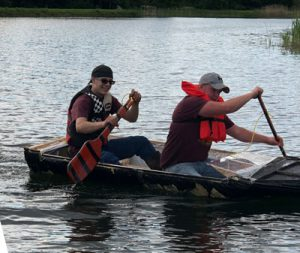 two boys paddling a homemade boat