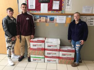 students standing in front of christmas boxes they made for the troops
