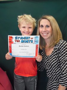student hold certificates with principal