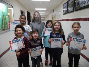 elementary age students holding up certificate for being student of the month