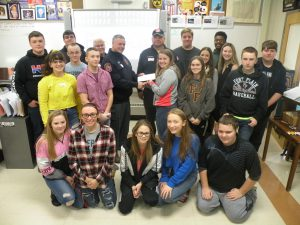 High School students posing with local fire department with their donations