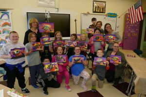 third grade class showing off their paintings
