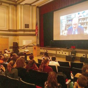video chat with an engineer is projected on a screen in a high school auditorium