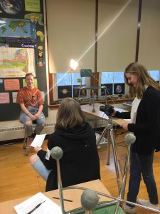 a high school student uses a video camera while another conducts an interview with a third student in a high school science classroom