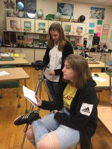 a high school student uses a video camera while another conducts an interview in a high school science classroom