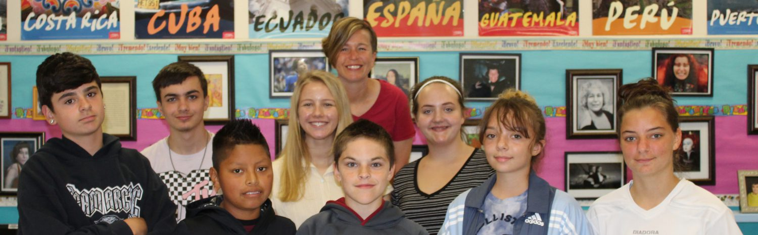 group of eight students and a teacher in front of spanish posters in a high school classroom