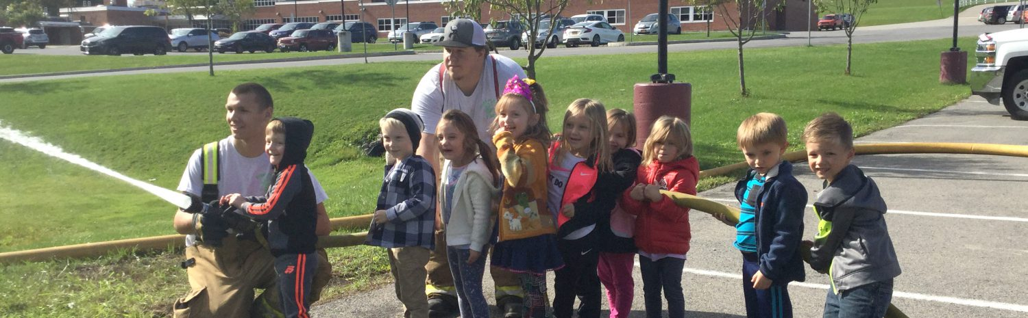 a firefighter helps a pre-k student spray a fire hose as the classmates hold up the hose behind them outside of an elementary school