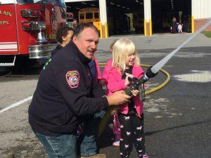 firefighter helps a pre-k student spray a fire hose outside of a school transportation building