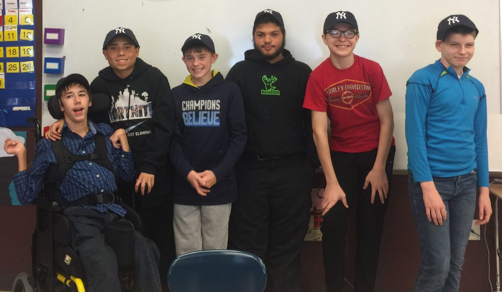 six students in yankees hats stand before a whiteboard in a classroom