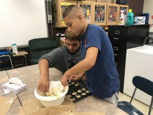 two students place batter from a bowl into a muffin pan at a table in a school classroom