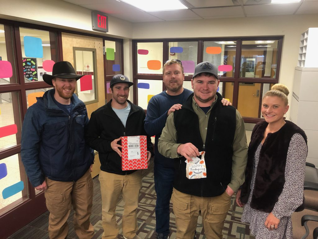 four company representatives and a school counselor hold up gift cards