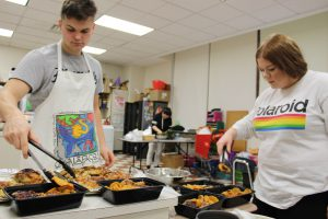 two high school students spoon barbecue chicken into take-out containers in a high school food science classroom