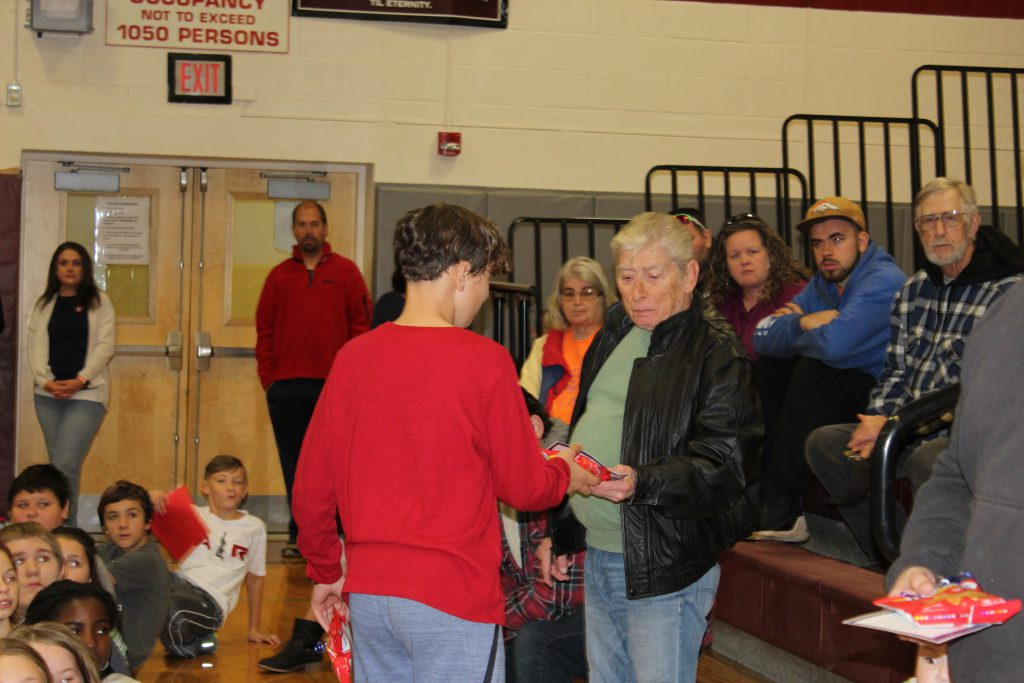 elementary student hands a veteran a small gift in a school gymnasium