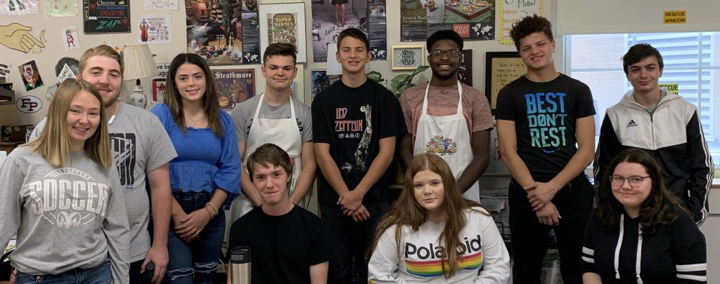 group of high school students pose for a photo in a food science classroom