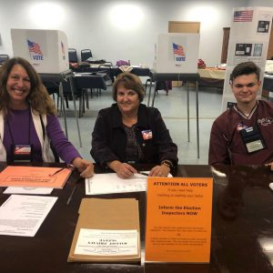 two adults and a high school student sit at a table at a poll site in a senior center