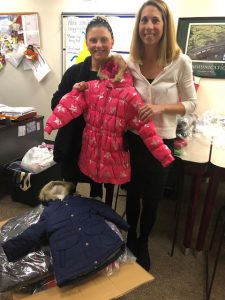 school counselor and principal hold up child's winter coat
