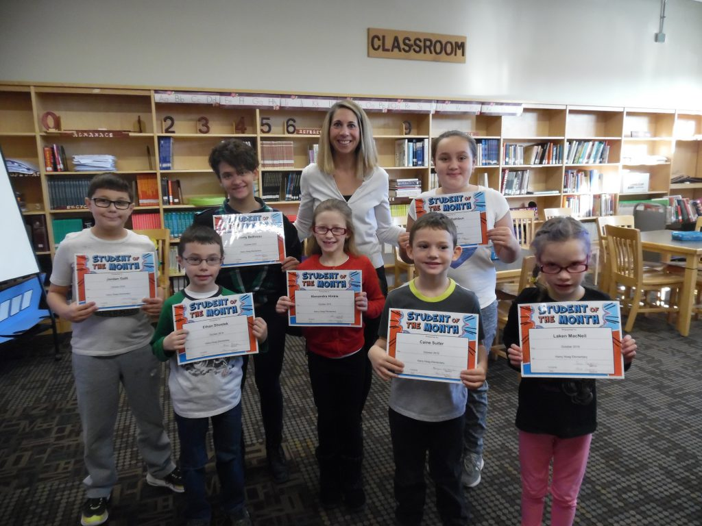 Seven students and an elementary school principal stand in two rows in a school library