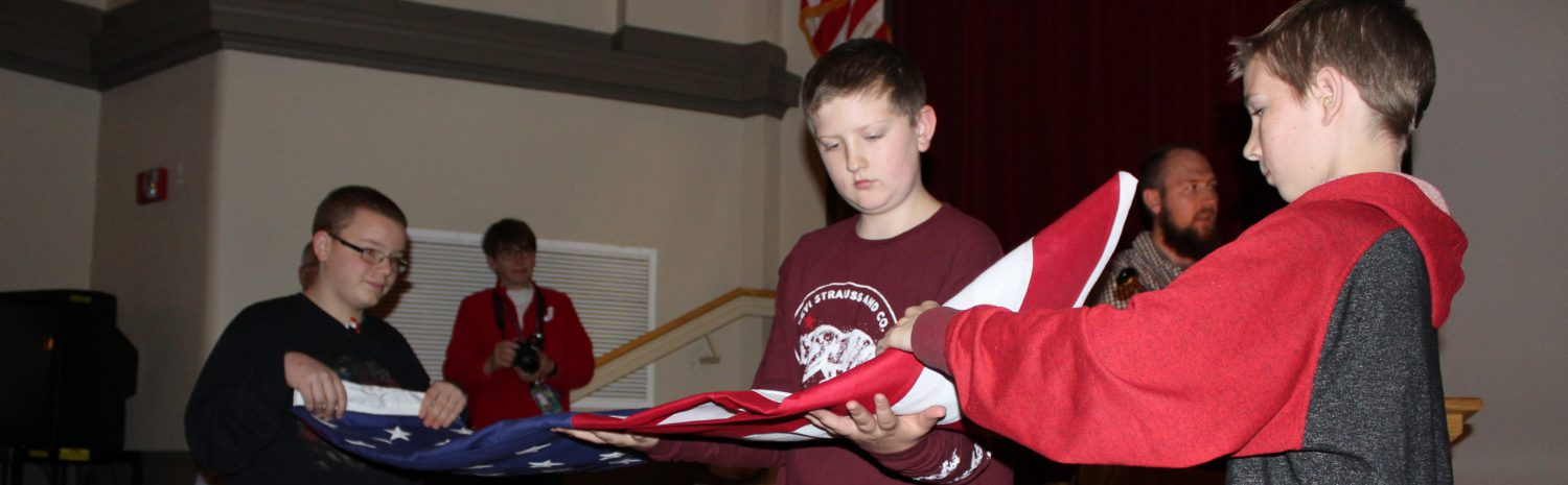 three seventh graders show the proper way to fold an American flag in a school auditorium