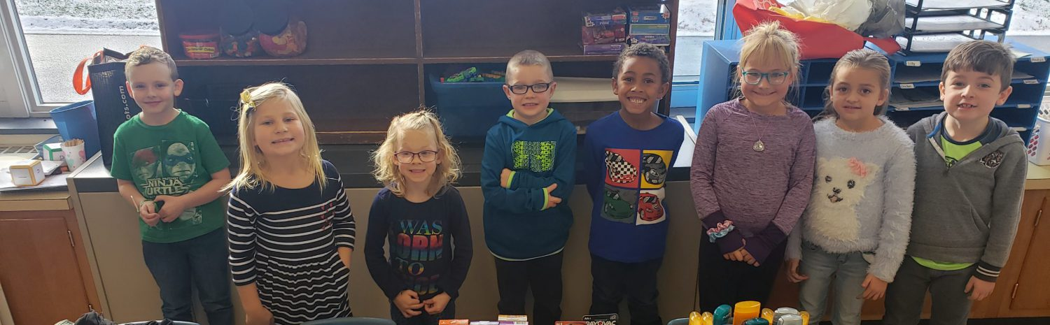 eight first grade students stand behind a table filled with donated items such as pens, candy, puzzle books and personal care items