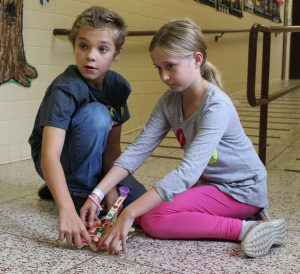 students kneeling on floor in school hallway while launching a catapult made of popsicle sticks