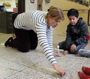 teacher and student kneel on the floor of a school hallway while using a tape to measure the distance between a catapult and a marshmallow pumpkin