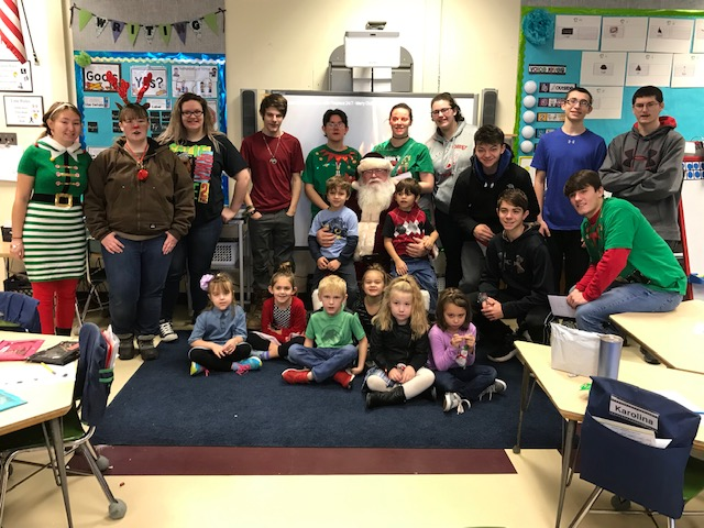 group picture of senior class members with kindergarten students and Santa Claus in an elementary classroom
