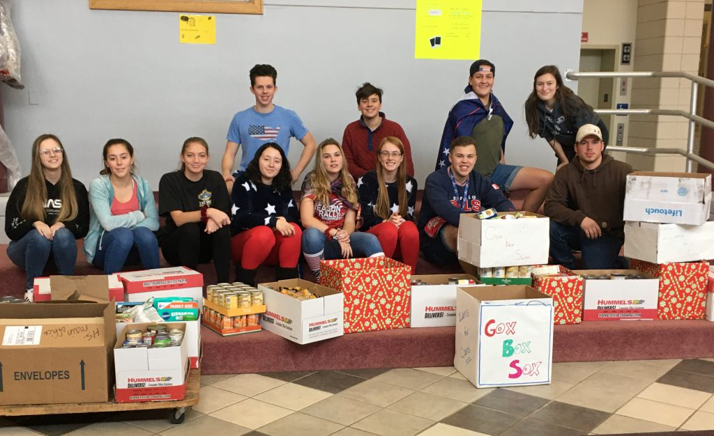 group of high school students sit in a school foyer with boxes of canned goods