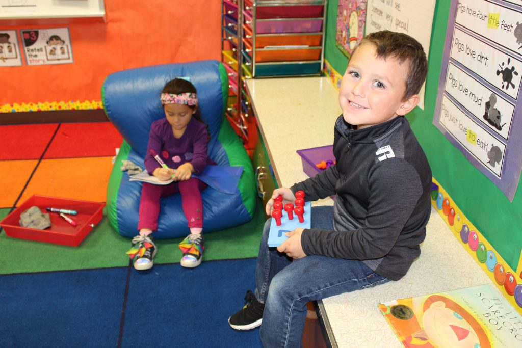kindergarten student sits on a bean bag while a classmate is seated on a counter