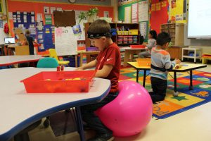 kindergarten student sits on an exercise ball