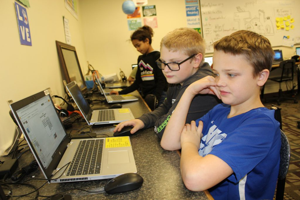 students seated at laptops in an elementary school computer lab